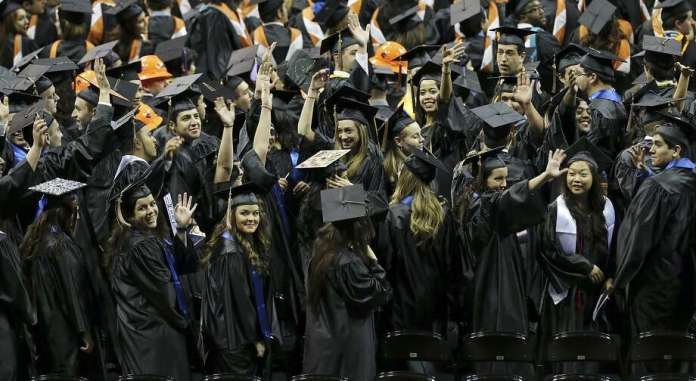 """University of Texas at San Antonio graduates wave to family and friends during the commencement ceremonies in December 2013 at the Alamodome. The Bureau of Labor Statistics says the value of a university degree is """"softening."""" Photo: Edward A. Ornelas /San Antonio Express-News / © 2013 San Antonio Express-News"""