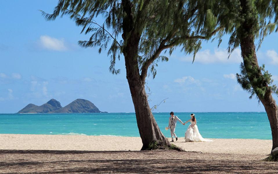 Όταν τα καλά νέα είναι κακά μαντάτα. Ως η καλύτερη δημόσια παραλία σε ολόκληρες τις ΗΠΑ ανακηρύχθηκε η Waimanalo Bay Beach Park. Οι κάτοικοι της μικρής πόλης αυτής πόλης της Χαβάης υποδέχθηκαν την βράβευση με ανάμικτα συναισθήματα. Χαρά που η παραλία της πόλης τους έγινε διάσημη και σκεπτικισμό σχετικά με τον κόσμο που θα συρρεύσει για να την απολαύσει. Στην φωτογραφία ένα ζευγάρι από την Ιαπωνία έσπευσε να φωτογραφηθεί μετά την βράβευση, βγάζοντας τις νυφικές τους φωτογραφίες  με φόντο τα καταγάλανα νερά. (AP Photo/Jennifer Sinco Kelleher)
