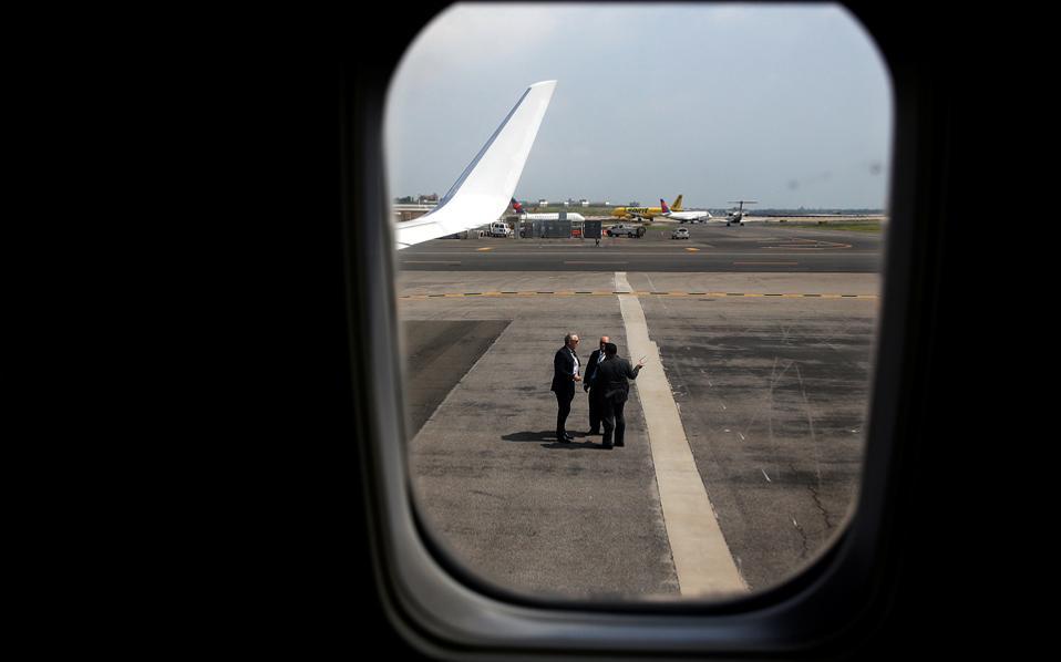 Πράκτορες της μυστικής υπηρεσίας, που είναι επιφορτισμένη με την ασφάλεια του προέδρου στο αεροδρόμιο La Guardia της Νέας Υόρκης, όπως φαίνονται μέσα από το ιδιωτικό αεροσκάφος του Ντόναλντ Τραμπ.