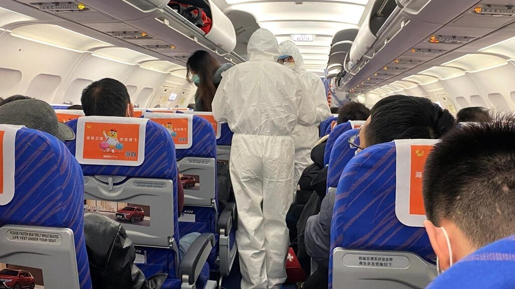 Nhân viên y tế Trung Quốc kiểm tra thân nhiệt hành khách trong một chuyến bay từ thành phố Trường Sa (Changsha), Hồ Nam, đến Thượng Hải, ngày 25/01/2020.