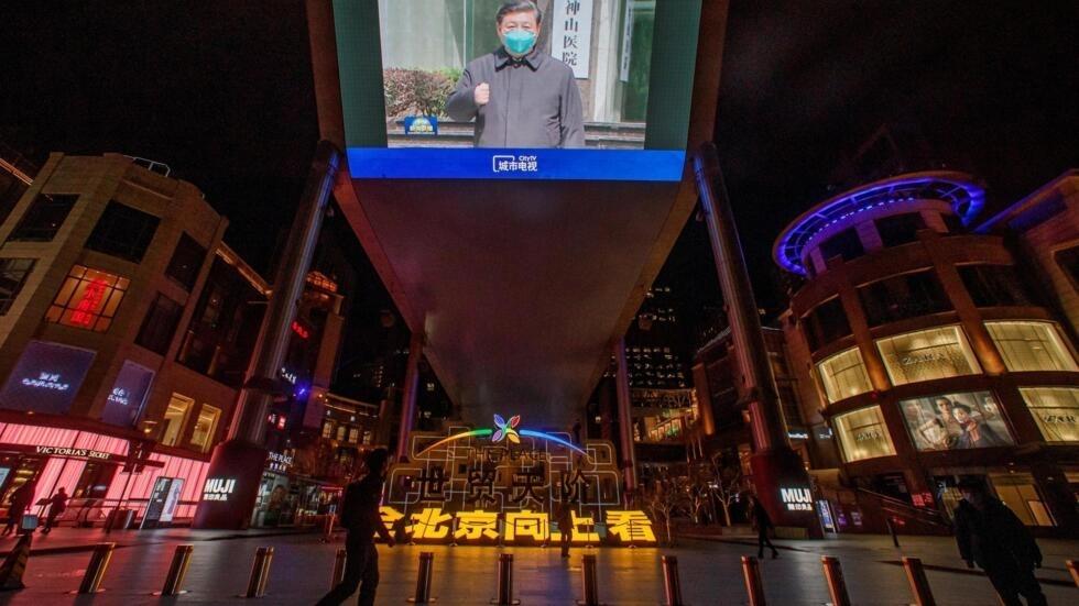 Hình ảnh Tập Cận Bình đi thăm Vũ Hán được chiếu trên màn ảnh rộng trước một trung tâm thương mại ở Bắc Kinh, Trung Quốc, ngày 10/03/2020