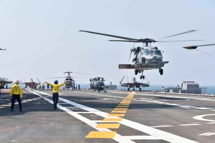 Helicopters land on an aircraft carrier during the second phase of Naval Exercise Malabar, a joint exercise involving India, the United States, Japan and Australia, in the northern Arabian Sea, on Tuesday, November 17, 2020. The navies of India and the United States, Australia and Japan held exercises in the northern Arabian Sea on Tuesday as part of the second phase of a naval exercise seen as part of a regional initiative to counter China's growing assertiveness in the Indo-Pacific.