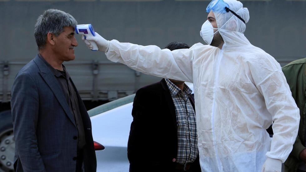 A equipe médica verifica a temperatura das pessoas em um ponto de passagem nos arredores de Duhok, Iraque, em 2 de março de 2020.
