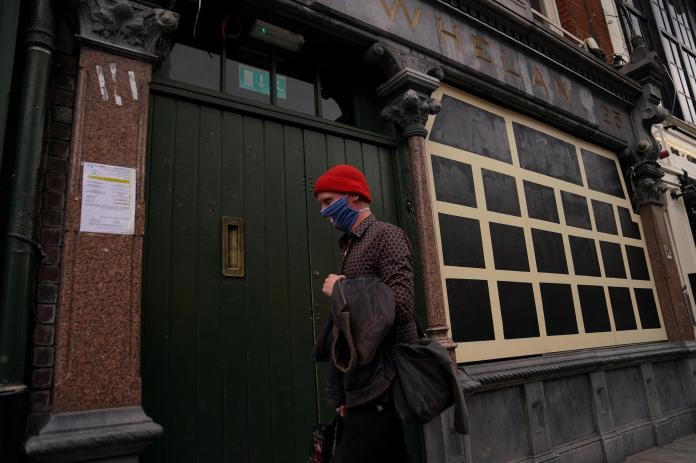 A person wearing a mask walks past a closed pub in Dublin city center on September 3, 2020.