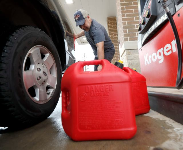 """Paul Villagomez loads filled gas containers into his truck as he prepares for Tropical Storm Nicholas, Monday, Sept. 13, 2021, in Kingwood, Texas. """"I'm just trying to be prepared,"""" Villagomez said. """"I'm actually surprised there aren't more people filling up."""" (Jason Fochtman/Houston Chronicle via AP)"""
