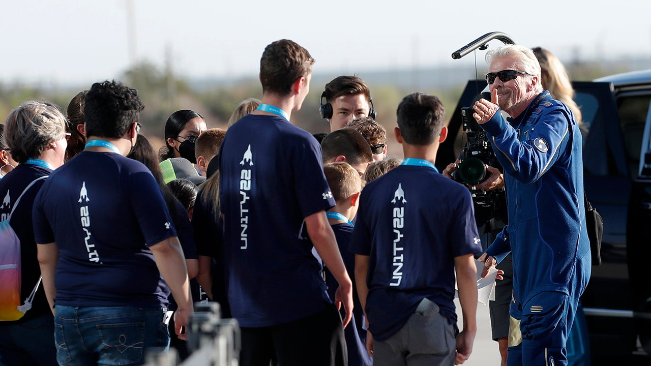 Virgin Galactic founder Richard Branson, right, is greeted by school children before heading to board the rocket plane that will fly him to the edge of space from Spaceport America near Truth or Consequences, New Mexico, on Sunday, July 11, 2021. (AP Photo/Andres Leighton)
