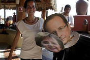 Oxfam activist displays masks of Angela Merkel and Francois Hollande near G-20 summit site in Los Cabos, Mexico.