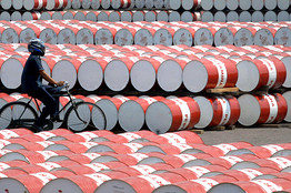 A file photo taken on May 6, 2008 shows a worker of state oil company Pertamina cycling past barrels filled with fuel in Jakarta