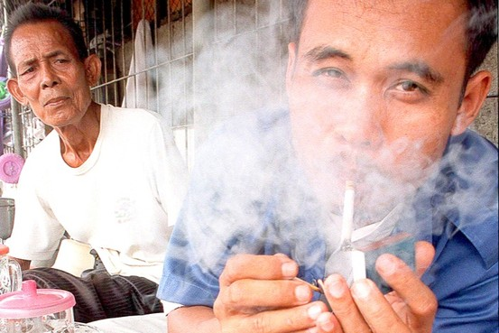 an Indonesian exhales smoke from his clove.