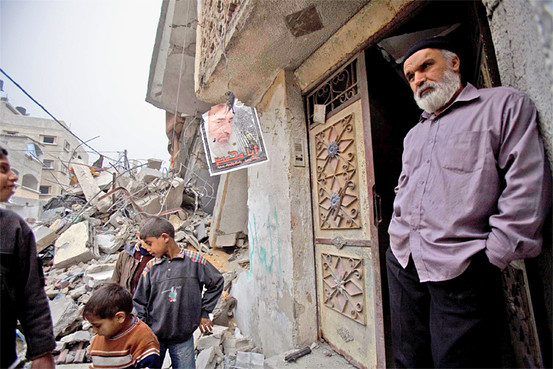 A poster of the late Sheikh Yassin hangs near a building destroyed by the Israeli assault on Gaza.