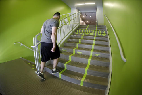 A Utah Valley University student walks up the bright green lanes painted on the stairs to the gym Thursday, June 18, 2015, at Utah Valley University, in Orem, Utah. Utah Valley University spokeswoman Melinda Colton said the green lanes were intended as a lighthearted way to brighten up the space and get students' attention. (AP Photo/Rick Bowmer)