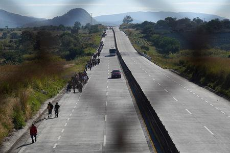 FILE PHOTO: A migrant, part of a caravan of thousands traveling from Central America en route to the United States, walk on the motorway on the outskirts of Guadalajara