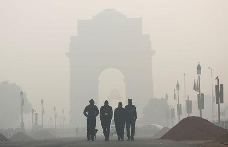 FILE PHOTO: Men walk in front of the India Gate shrouded in smog in New Delhi, India, December 26, 2018. REUTERS/Adnan Abidi