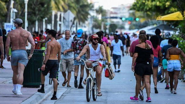 PHOTO: A man rides a bicycle as people walk on Ocean Drive in Miami Beach, Fla. on June 26, 2020. (Chandan Khanna/AFP via Getty Images)
