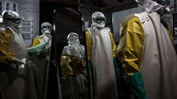 PHOTO: Health workers are seen putting on their personal protective equipment before entering the red zone of a Medecins Sans Frontieres supported Ebola treatment center in Butembo, Congo, Nov. 3, 2018. (John Wessels/MSF via AP)