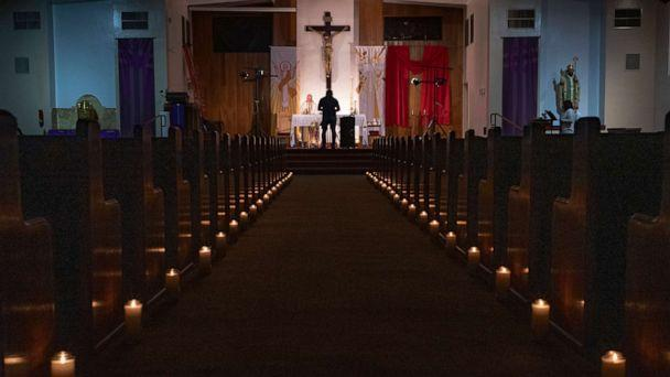 PHOTO: Pastor Nicolas Sanchez celebrates Easter Vigil Mass at his church decorated with candles and pictures sent by his parishioners attached to their pews at St. Patrick Church in North Hollywood, Calif., April 11, 2020. (Damian Dovarganes/AP, FILE)
