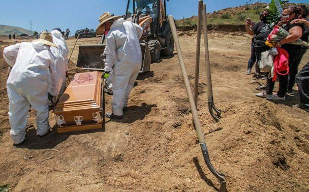 PHOTO: In this May 5, 2020 photo, workers in full protective gear, unload a coffin that contain the remains of a person who died from the new coronavirus, in an area of the municipal cemetery set apart for victims of COVID-19, in Tijuana, Mexico. (Joebeth Terriquez/AP, File)