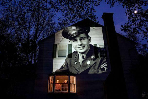 PHOTO: An image of veteran James Sullivan is projected onto his son Tom Sullivan's house on the left as he looks out the window with his brother Joseph Sullivan in South Headley, Massachusetts, May 4, 2020. (David Goldman / AP, FILE)