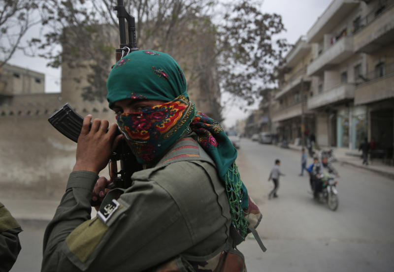 FILE -- In this file photo taken on Wednesday, March 28, 2018, a member of the Kurdish internal security forces holds his weapon during a patrol in Manbij, north Syria. The planned U.S. troop withdrawal opens a void in the north and east of Syria, and the conflicts and rivalries among all the powers in the Middle East are converging to fill it. (AP Photo/Hussein Malla, File)