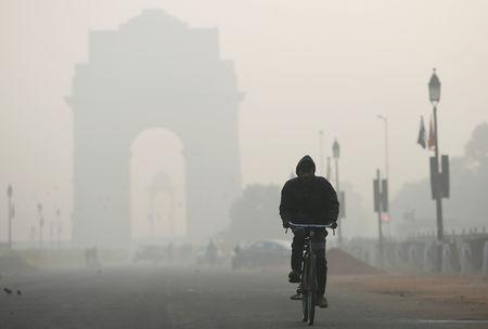 FILE PHOTO: A man rides his bicycle in front of the India Gate shrouded in smog in New Delhi, India, December 26, 2018. REUTERS/Adnan Abidi
