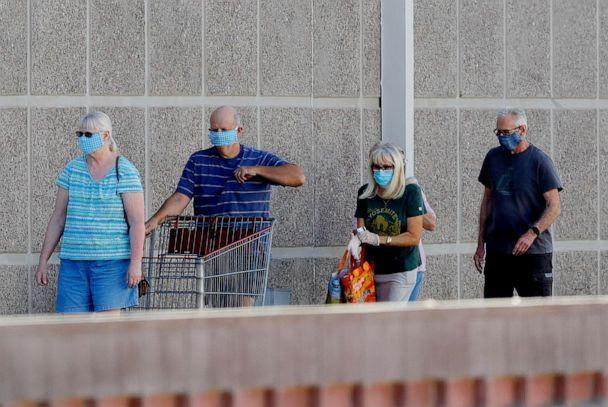 PHOTO: Customers wear masks while waiting to enter a store on June 17, 2020 in Tempe, Arizona (Matt York / AP)