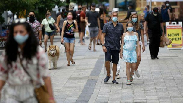 PHOTO: Pedestrians wear masks out of concern for the coronavirus, June 28, 2020, while walking along a sidewalk, in Boston. (Steven Senne/AP)