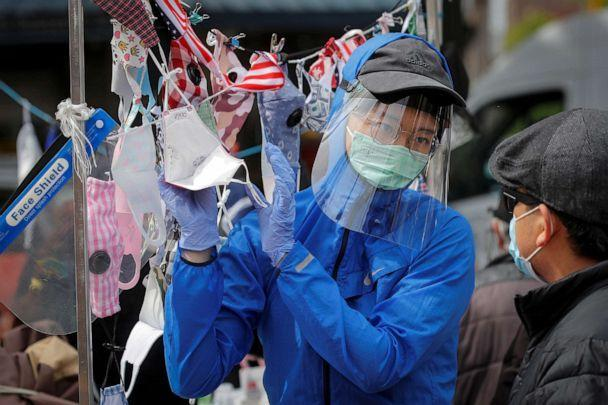 PHOTO: a man talks to a street vendor about face masks during an outbreak of coronavirus disease in Queens, New York, May 19, 2020. (Brendan McDermid / Reuters)