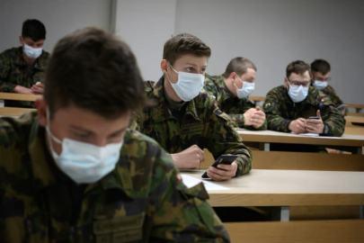 Swiss soldiers install the coronavirus tracing app on their smartphones (AFP Photo/FABRICE COFFRINI)
