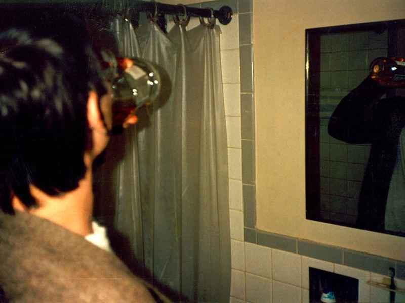 Un joven degusta un chupito de colutorio frente al espejo.