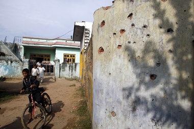 A boy cycles past a wall damaged in alleged firing from the Pakistan side of the Kashmir border, at Mawa village, in Samba district, about 58 kilometers south of Jammu, on Saturday, 24 October, 2015. AP