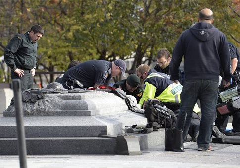 Emergency personnel tend to a soldier shot at the National Memorial near Parliament Hill in Ottawa / AP