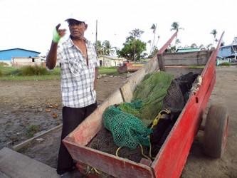 Christandat Jadundan explains how the fish pen is raised.  (Photo by Jannelle Williams)