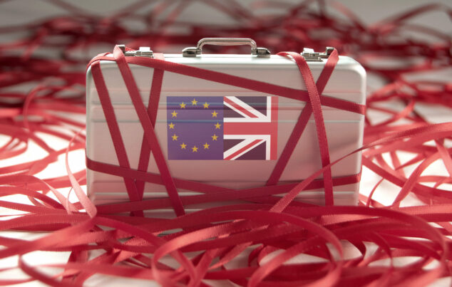 Suitcase With Eu And Union Jack Flags On Side Wrapped Up In Red Tape, Eu One-Stop-Shop Concept
