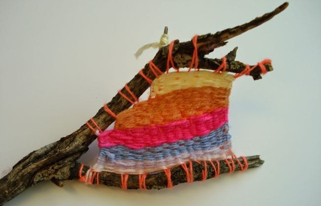 Forked stick with yarn stripes woven between the twigs