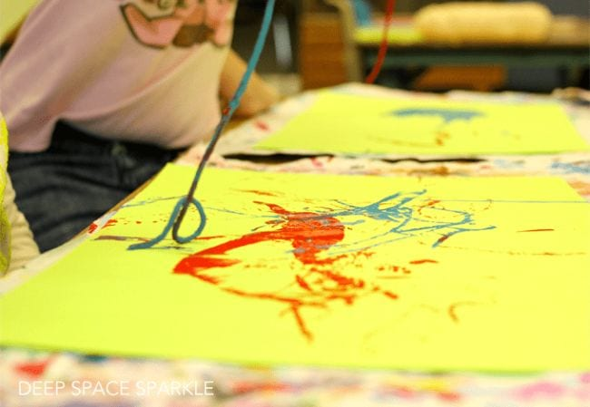 First grade art student pulling paint-covered yarn along a piece of paper