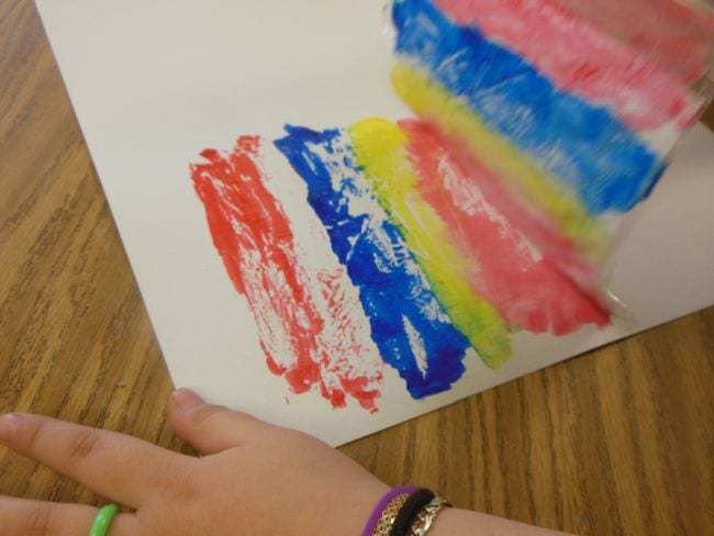 Student using a plastic bag to print paint stripes on a piece of paper