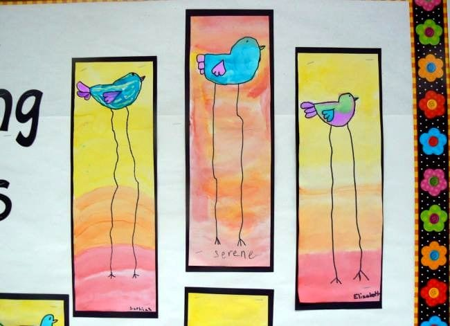 Long-legged blue birds on a watercolor background of yellow, orange, and pink