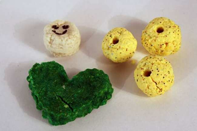 Green plastic heart and yellow beads made from milk caseins