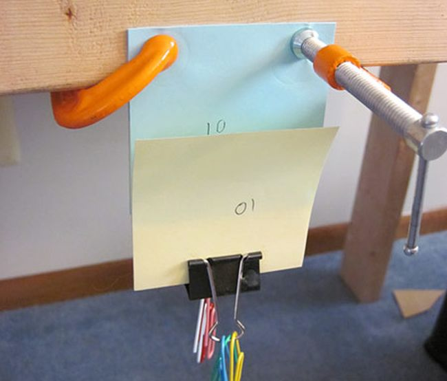 Orange clamps holding sticky notes to a piece of wood, with a binder clip at the bottom holding paper clips (Eighth Grade Science)