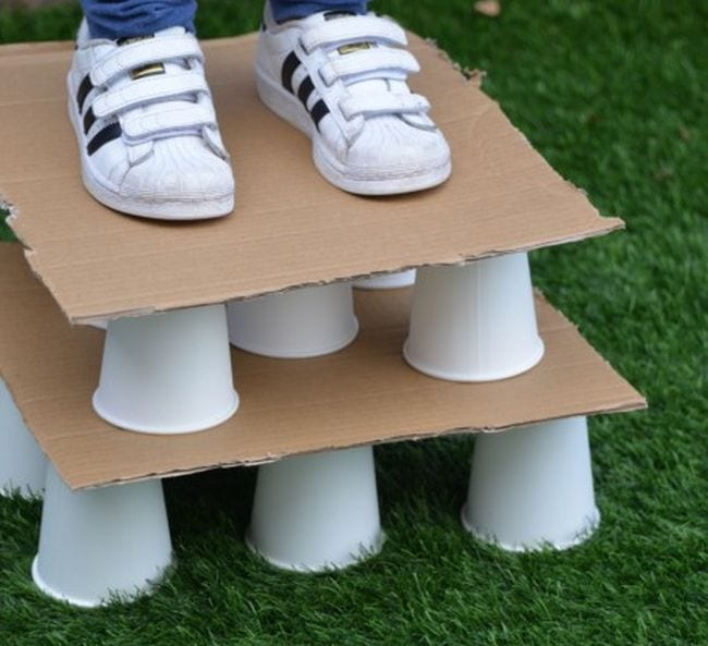 Student standing on top of a structure built from cardboard sheets and paper cups