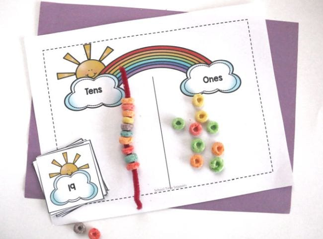 Worksheet with rainbow and clouds on each end, labeled ones and tens, with pipe cleaner strung with Froot Loops and handful of loose cereal