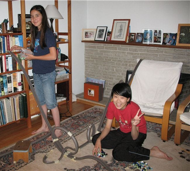 Two students building a marble roller coaster from foam insulation tubes