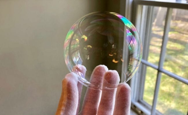 Student's gloved hand holding a soap bubble next to a window (Fourth Grade Science)