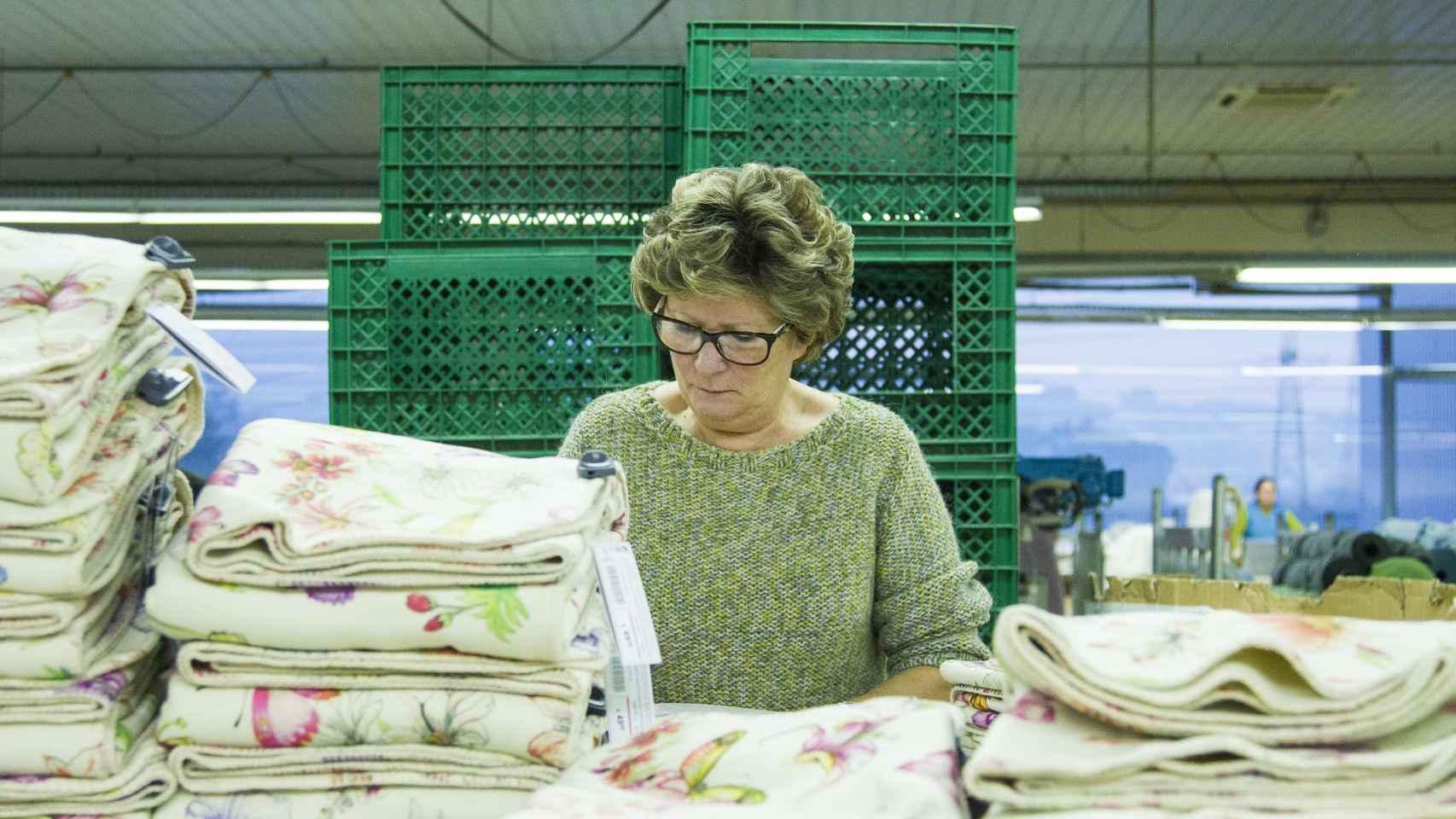 Una trabajadora de Crispim Abreu dobla mantas que se venderán en Zara Home.
