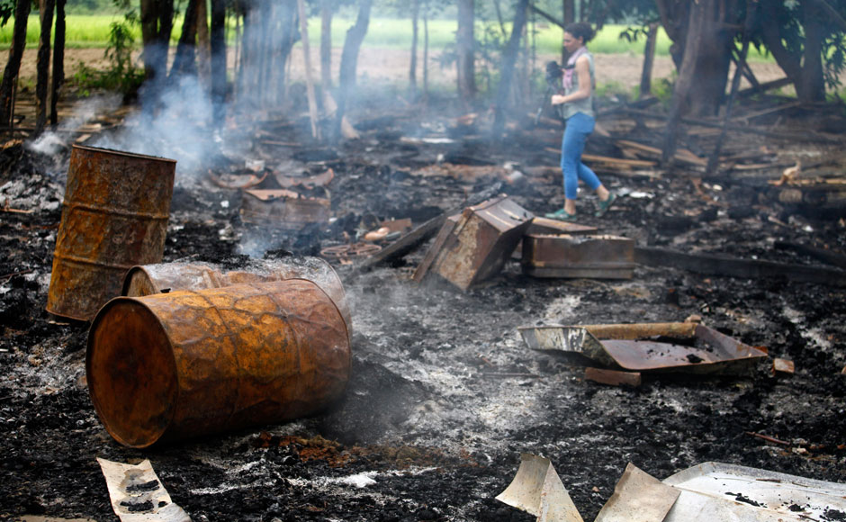 A journalist walks amongst the burnt-out remains of houses at Shwe Lay village, outside of Thandwe in Rakhine state, October 2, 2013. Security forces raced to contain deadly violence in Myanmar's Rakhine state on Tuesday, police said, after mobs torched Muslim homes and Buddhist villagers were attacked in a region plagued by intractable sectarian tensions. According to the police, at least five Muslims have died in the violence. REUTERS/Soe Zeya Tun