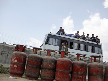 Nepalese people sit on top of a crowded bus as it passes near lined cooking gas cylinders in Kathmandu. AP