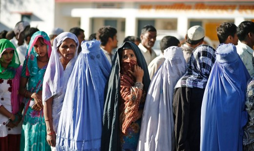 Muslim women, who were displaced by deadly religious strife last year, stand in a queue to cast their votes for the general election at a polling station in Palra village in Muzaffarnagar district in the northern Indian state of Uttar Pradesh April 10, 2014. The election is spread out over five weeks, with voting ending on May 12. It was the turn of voters in Delhi, the capital, on Thursday and many parts of Uttar Pradesh, including Muzaffarnagar, where Narendra Modi's popularity is running high and Muslims are worried about their future. For many of the 815 million registered to vote, Modi and his Bharatiya Janata Party (BJP) represent a promise of better governance, industrial growth and job creation. REUTERS/Anindito Mukherjee (INDIA - Tags: POLITICS ELECTIONS RELIGION) - RTR3KO7G