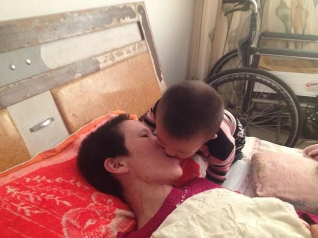Gai Qianbo ajuda a mãe Zhang Rongxiang a se alimentar, mastigando os alimentos e colocando-os em sua boca. (Foto: QCH/The Grosby Group)