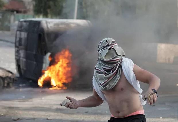 Em foto do dia 30 de outubro, palestino mascarado lança pedra contra forças de segurança israelenses em Jerusalém (Foto: Ahmad Gharabçi/AFP)