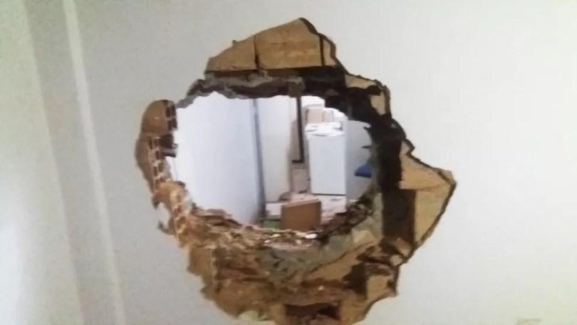 Ainda em Brejinho, criminosos usaram uma marreta para abrir um buraco na parede da lotérica — Foto: Redes sociais